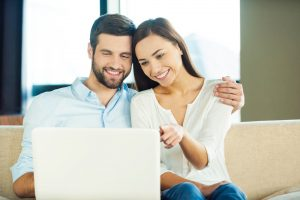 A happy couple using computer together